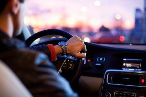 Autofahrer, von hinten fotografiert, lenkt ein Fahrzeug.