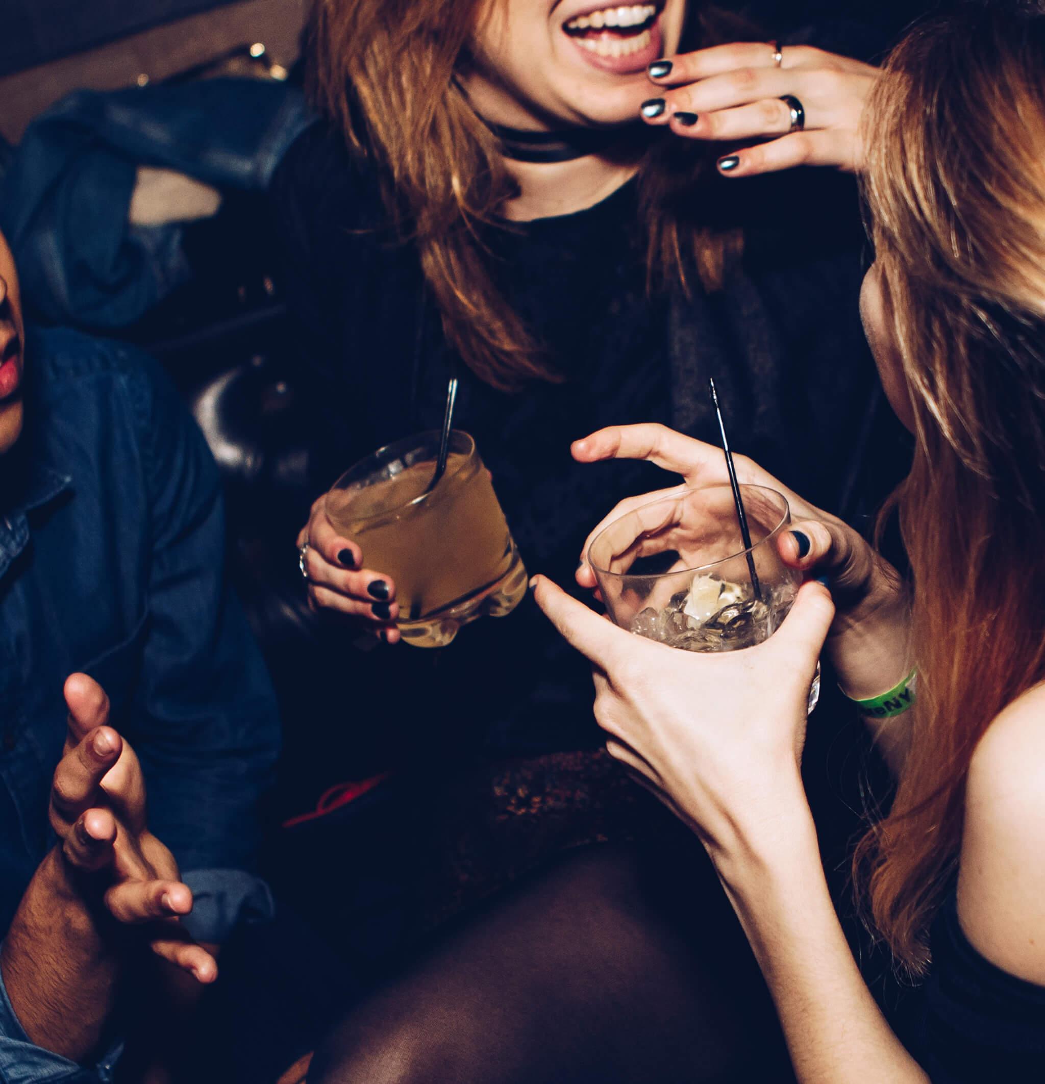 Zwei Frauen und ein Mann mit alkoholischen Getränken in gelöster Stimmung.